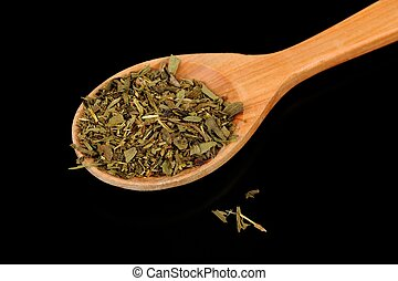 A pile of dried herbes de Provence (a mixture of dried herbs typical of Provence) in a wooden spoon against a black background