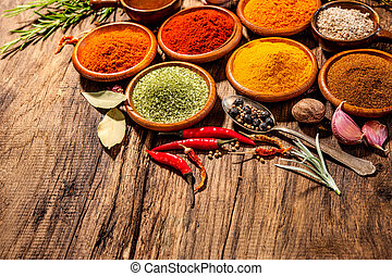 Herbs and spices on wooden table - Various herbs and spices ...