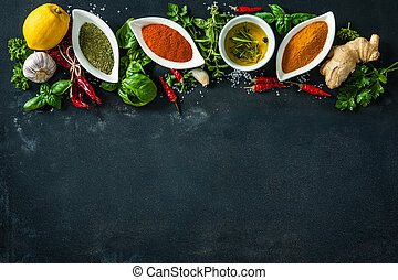 Herbs and spices over black stone background. Top view with ...