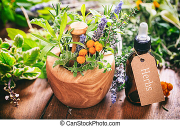 Herbs, essential oil and mortar on wooden background