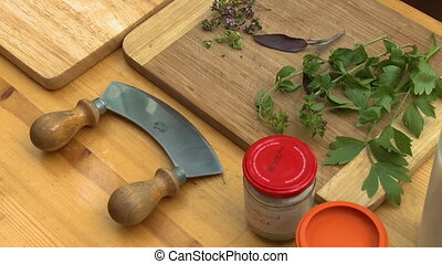 Herbs on Cutting Board Next to Mezzaluna Knife - Steady,...