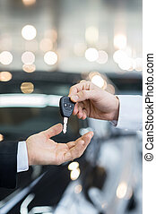 Here is your key! Close up of man giving key to the car owner while standing in front of a car