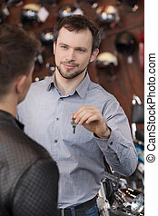 Here is your key. Confident young sales executive giving the key to motorcycle owner