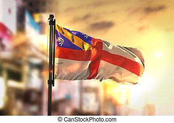 Herm Flag Against City Blurred Background At Sunrise Backlight