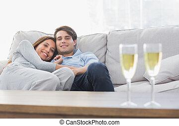 hermoso, descansar, pareja, sofá, flautas champaña
