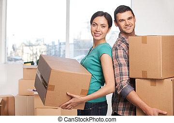 hermoso, el estar parado sonriente, pareja, joven, nuevo, mientras, cajas, cámara, mudanza, tenencia, cada, cierre, apartment., cartón, otro