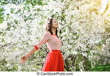 hermoso, feliz, mujer joven, el gozar, olor, florecimiento, primavera, jardín