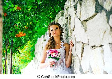 hermoso, joven, novia, posición, en, un, pared de piedra, plano de fondo