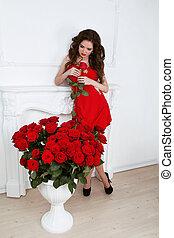 hermoso, morena, mujer, con, ramo, de, rosas rojas, flores, en, moderno, interior, apartamento, valentines, day.