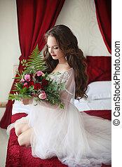 hermoso, morena, novia, retrato de la boda, tenencia, rosas, ramo, de, flowers., mujer sonriente, con, pelo rizado, estilo, llevando, en, blanco, sexy, tocador, bata, posar, en, rojo, cama, room.