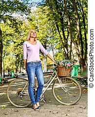 hermoso, mujer joven, en, bicicleta, en el estacionamiento