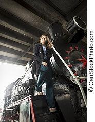 hermoso, mujer joven, posar, en, grande, negro, vapor, locomotora