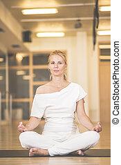 hermoso, mujer joven, sentado, en, lotos, postura, y, practicar, meditación, en, yoga, vestíbulo