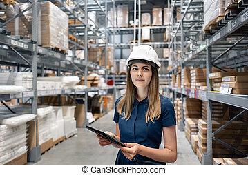hermoso, mujer joven, trabajador, de, almacén de muebles, en, compras, center., niña, buscar, bienes, con, un, tableta, es, verificar, inventario, niveles, en, un, warehouse., logística, concepto