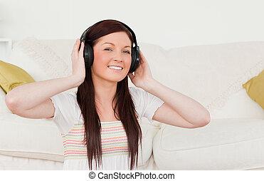 hermoso, mujer pelirroja, escuchar música, con, auriculares, mientras, sentado, en una alfombra, en, el, sala