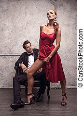 hermoso, niña, en, vestido rojo, tratar, para seducir, guapo, man., actuación, ella, esbelto, pierna