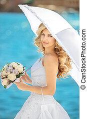 hermoso, novia, mujer, con, paraguas blanco, y, rosas, ramode flores, posar, encima, seafront, en, soleado, day.