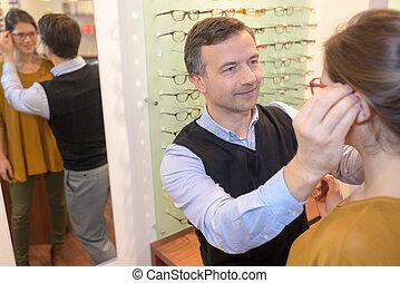 hermoso, oftalmólogo, morena, hembra, escoger, óptica, tienda, anteojos