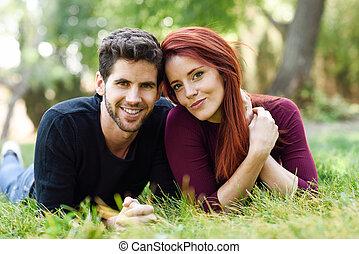 hermoso, pareja joven, colocar, en, pasto o césped, en, un, urbano, park.