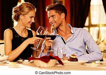 hermoso, pareja joven, con, copas de vino tinto, en, lujo,...
