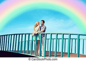 hermoso, pareja joven, enamorado, en, el, puente, encima, cielo azul, y, colorido, rainbow., día de valentín, y, relaciones, concepto