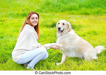 hermoso, perro cobrador dorado, perro, da, pata, dueño, en la hierba, en, soleado, día de verano
