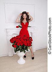 hermoso, sexy, morena, mujer, en, vestido rojo, posar, cerca, ramo de rosas, flores, en, moderno, interior, apartamento