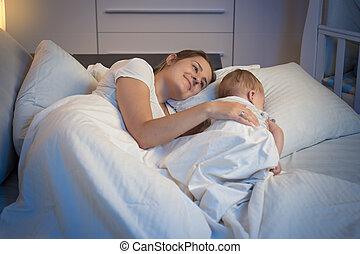 hermoso, tiro, ella, noche, cama, madre, bebé, sonriente, acostado