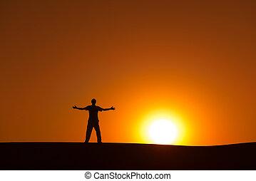 Heroic achievement by men - Man at orange sunset in desert...