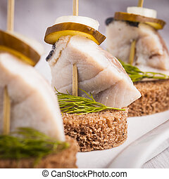 Herring canape with onion, pickled cucumber and dill