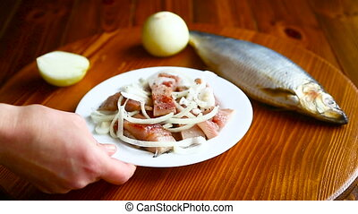 Herring salad with onion on a wooden table