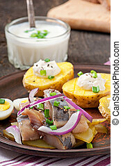 Herring salad with onions and baked potato