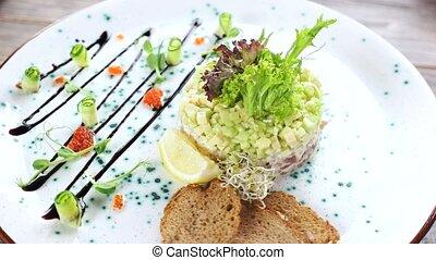 Herring tartare with fresh lettuce. Tasty restaurant food.