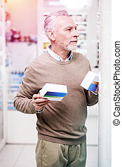 Hesitating buyer holding medications in two hands