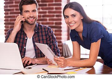 het behouden, vriendelijk, atmosfeer, op, work., vrolijk, jonge man, en, vrouw zitten, op, de, werkende plaats, en, het glimlachen, terwijl, vrouwenholding, digitaal tablet, en, mens het spreken, op, de, mobiele telefoon
