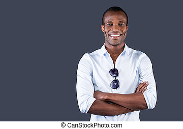 het charmeren, handsome., mooi, jonge, zwarte man, in, blauw hemd, het behouden, gekruiste wapens, en, het glimlachen, aan fototoestel, terwijl, staand, tegen, grijze , achtergrond