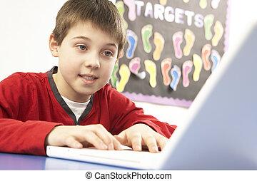 het gebruiken computer, informatietechnologie, schooljongen, stand