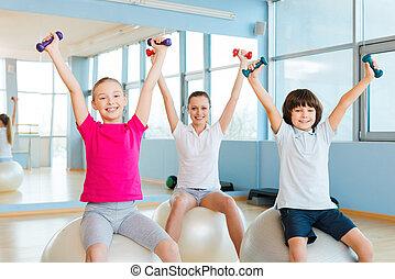 het genieten van, gezonde , lifestyle., vrolijk, moeder, en, twee kinderen, het uitoefenen, met, dumbbells, in, gezondheid club, terwijl, zittende , op, de, fitness, gelul
