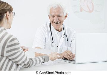 het glimlachen, arts, gebruikende laptop