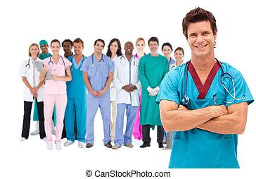 het glimlachen, chirurg, met, medisch personeel, achter, hem