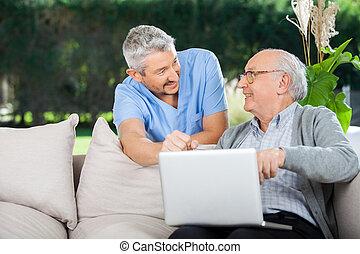 het glimlachen, draagbare computer, gebruik, senior, verpleegkundige, man