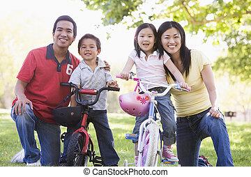 het glimlachen, fietsen, kinderen, gezin, buitenshuis