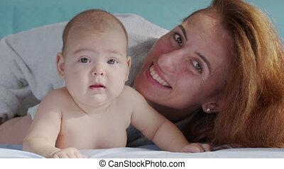 het glimlachen, genieten, home., vrolijke , zuigeling, jongen, schattig, bed, gezin, mooi, verslappen, bedroom., samen, gezondheidszorg, concept., spelend, pasgeboren, kindertijd, ouder, kaukasisch, baby, moeder