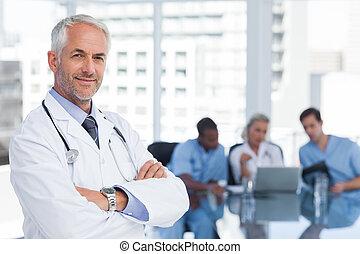het glimlachen, gevouwen wapens, arts