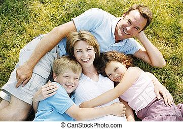het glimlachen, gezin, het liggen, buitenshuis