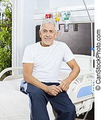 het glimlachen, hogere mens, zitting op het bed, op, rehab, centrum