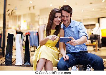 het glimlachen, jong paar, kijken naar, mobiele telefoon