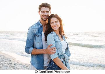 het glimlachen, jong paar, staand, aan het strand