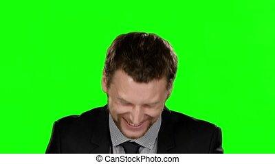 het glimlachen, jonge man, in, formeel, kostuum, kijken naar, de, camera., groene, scherm