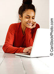 het glimlachen, jonge vrouw , gebruikende laptop, terwijl, het liggen op de verdieping
